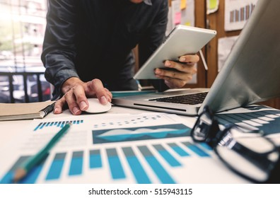 business documents on office table with digital tablet computer with smart phone and graph business digital diagram and businessman working in morning light