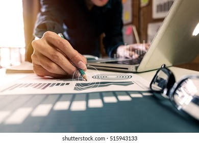 business documents on office table with digital computer laptop with smart phone and graph business digital diagram and businessman working in morning light