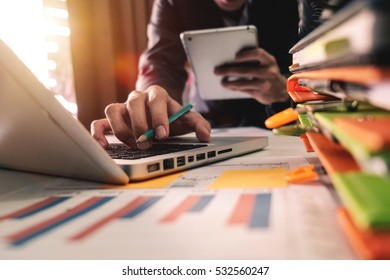 business documents on office table with smart phone and digital tablet and graph business with social network diagram and man working in the office