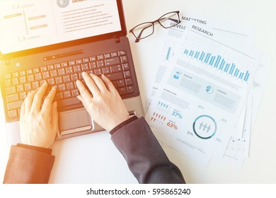 business documents on office table with laptop computer and graph financial diagram and Business people working at office