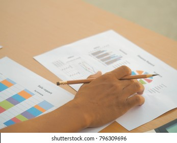 Business documents on office table with laptop computer and graph finance diagram and man working in the background.