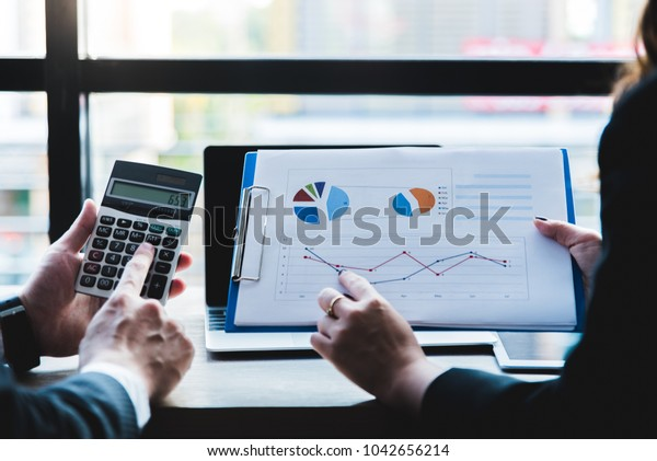 Business documents on office table with smart phone and digital tablet and graph financial.