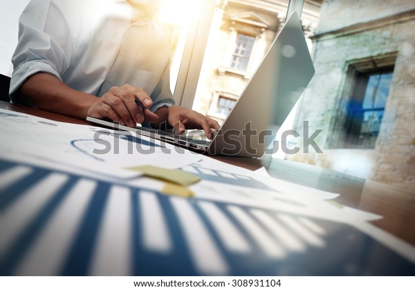 business documents on office table with smart phone and digital tablet and graph financial diagram and man working in the background
