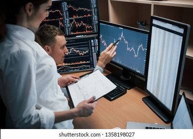 Business don't do itself, you need to struggle to achieve good results Team of stockbrokers are having a conversation in a office with multiple display screens.