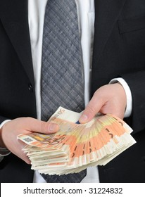 Business dressed man counts 50-euro banknotes
