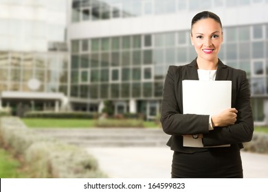 Business dressed woman with folder, standing in front of the building.