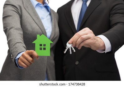 business, eco and real estate concept - businessman and businesswoman holding green house and keys