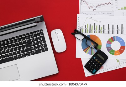 Business, economic analysis topic. Workspace of economist on red background. Laptop, graphs and charts with a calculator. Top view
