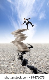 Business and Economic crisis concept. cracked road and  businessman unstable on the money tower