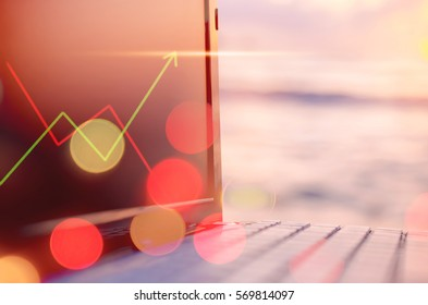 Business economic technology working concept. Keyboard notebook on tropical sunset beach double exposure graph money stock trading and colorful bokeh light background.Vintage filter effect color style