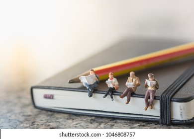 Business and education concept. Group of businessman miniature figures sitting and reading book and newspaper on black notebook with pencil.