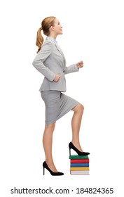 business and education concept - smiling businesswoman stepping on pile of books