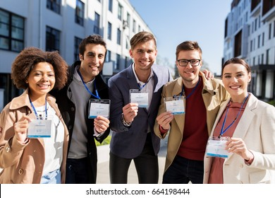 business, education and corporate concept - international group of people with conference badges on city street