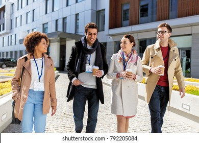business, education and corporate concept - international group of people with coffee and conference badges on city street