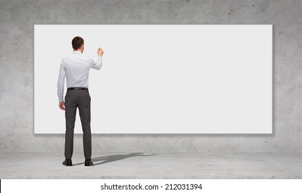 business, education and office people concept - businessman or teacher with marker writing or drawing something on white blank board over concrete wall background from back