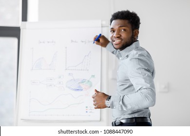 business, education and people concept - african american businessman with flip chart at office presentation