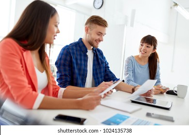 business, education and people concept - happy creative team or students with papers working at office