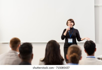 business, education and people concept - smiling businesswoman or teacher with microphone talking to group of students at conference presentation or lecture
