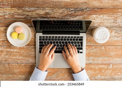 business, education, people and technology concept - close up of female hands with laptop computer, cookies and coffee cup on table