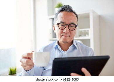 business, education, people and technology concept - businessman with tablet pc computer drinking coffee at office