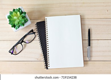 Business, education, still life, working or planning concept : Office desk table with open notebook paper, pen and eyeglasses, Flat lay or top view with copy space, ready for adding or mock up
