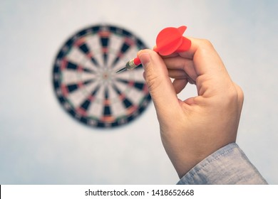 Business education success and target concept. Close up a hand is targeting the green dart arrow towards the center of dartboard. hit the target. Success in business.