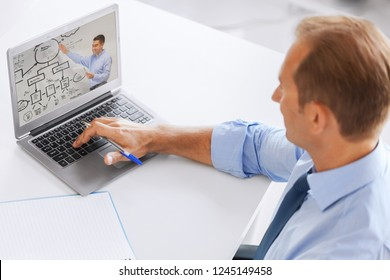 business, education and technology concept - businessman watching webinar on laptop computer at office
