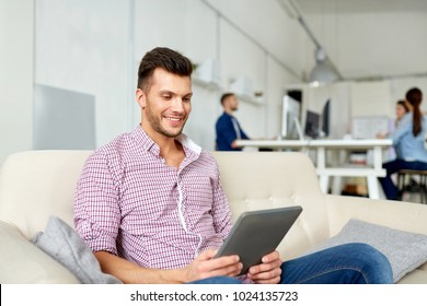business, education, technology and people concept - man in glasses with tablet pc computer working at office