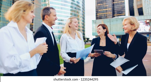Business employees talking with boss in La Defense Paris keeping laptop and document cases. Concept of successful management team members. Cheerful biz partners resting outside and speaking about good