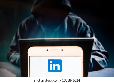 Business and employment oriented network and platform LinkedIn logo is seen on an Android mobile device with a figure of hacker in the background.