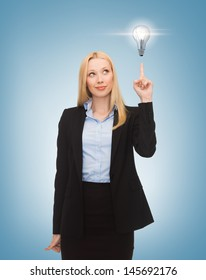 business, energy and environment concept - woman pointing at light bulb