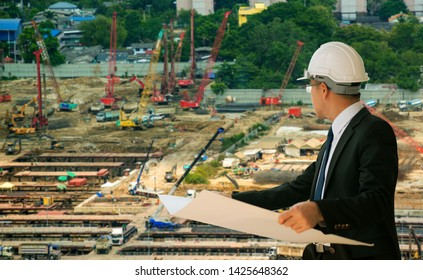 Business engineer planing at construction site with city background, young man architect on a building industry construction site,industry and business concept.