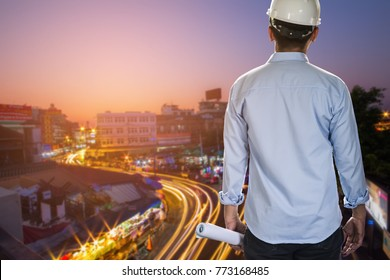 Business engineer planing at construction site with night city background. Construction concept.