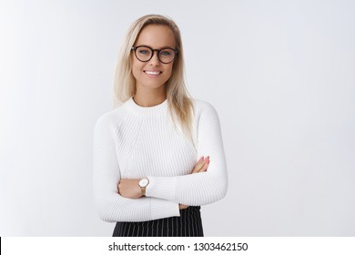 Business, entreprener and finance concept. Confident young female boss leading new project feeling determined and assured cross hands over chest and smiling accomplished over white background