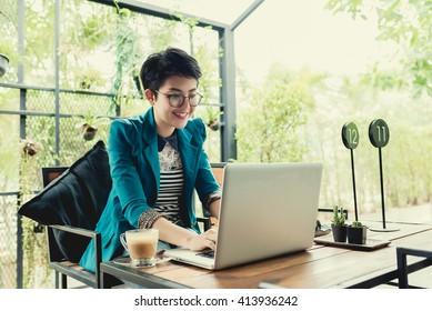 Business entrepreneur asian girl working online on laptop in cafe.