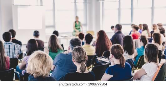 Symposium für Unternehmen und Unternehmertum. Muttersprachler, der auf Geschäftstreffen spricht. Publikum im Konferenzsaal. Hintere Ansicht eines nicht erkannten Teilnehmers im Publikum.