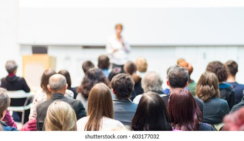 Business and entrepreneurship symposium. Female speaker giving a talk at business meeting. Audience in conference hall. Rear view of unrecognized participant in audience. Copy space on white screen.