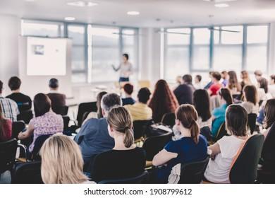 Symposium für Unternehmen und Unternehmertum. Sprecher, der auf Geschäftstreffen einen Vortrag hält. Publikum im Konferenzsaal. Hintere Ansicht eines nicht erkannten Teilnehmers im Publikum.