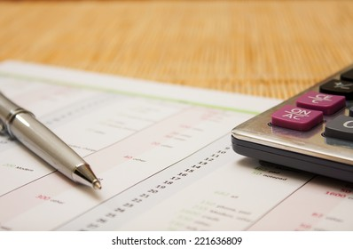 business environment. gray ballpoint pen, printed document and a large calculator on the table. Closeup.