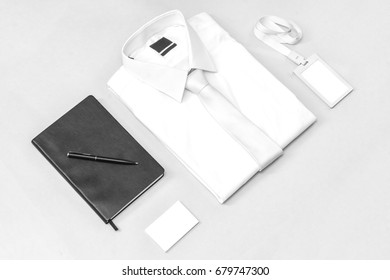 Business equipment on white table, shirt, tag, business card, note, pen, isolated