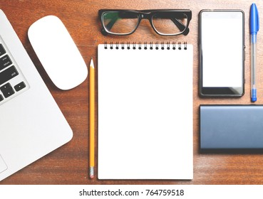 Business essentials. Top view of spiral blank notebook on wood desk background