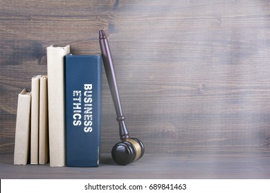 Business Ethics. Wooden gavel and books in background. Law and justice concept