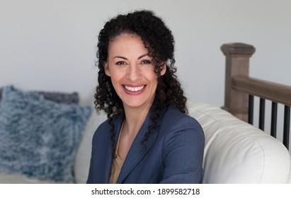 Ethnische Geschäftsfrau lächelt an der Kamera. Sitzen auf einem Sofa.