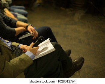Business event. The first row at a business event, forum, seminar. On his knees lies a book and a microphone in the hands of an elderly businessman