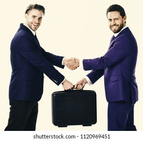 Business exchange between businessmen in suits. Successful deal concept. Handover of suitcase in hands of partners on white background. Businessmen with happy faces shaking hands and hold briefcase.