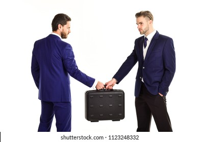 Business exchange concept. Handover of suitcase in hands of partners, isolated on white background. Businessmen with serious faces hold briefcase with cash. Business deal between businessmen in suits.