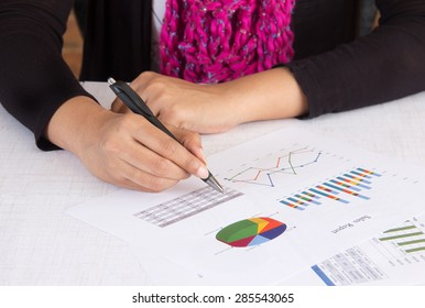 Business executive analyzing sales report with charts and graphs. Person wearing business casual wear in her office room. Concept for woman in business.