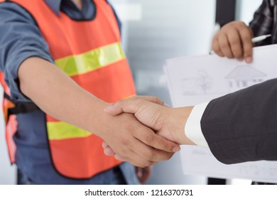 Business executive and architect hands shaking after successful deal a new construction project in meeting room.