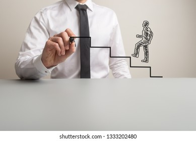 Business executive drawing steps for a handdrawn businessman to climb in a conceptual image. With copy space.