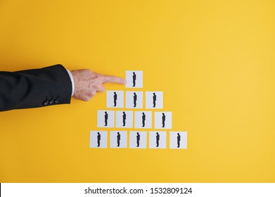 Business executive making a pyramid scheme of post it papers with businessman silhouette on them in a conceptual image. Over yellow background
